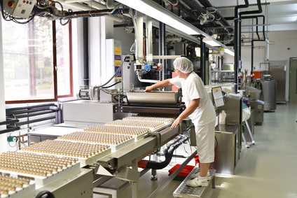 Frau bedient Maschine in der Lebensmittelindustrie - Fabrik zur Herstellung von Pralinen - Fliessband mit Süßwaren
